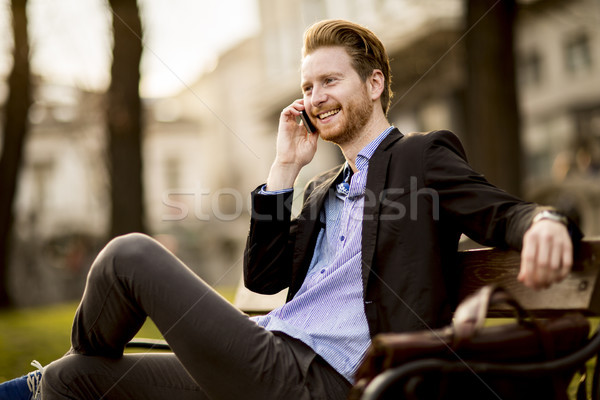Young redhair businessman with mobile phone on a bench Stock photo © boggy