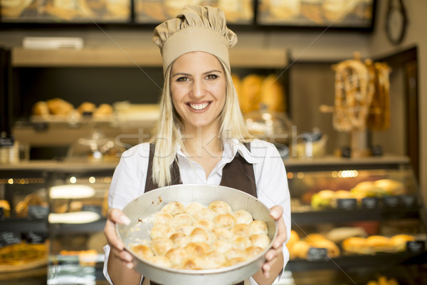 Stock photo: Woman who works in a bakery posing with a casserole in which the