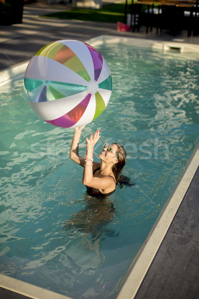 Stock photo: Young womans playing with a ball in the swimming pool