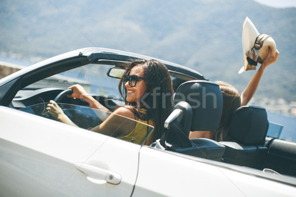 Young women in white cabriolet car driving everywhere and lookin Stock photo © boggy