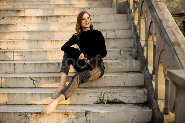 Young woman with mobile phone sitting at stairs outdoor Stock photo © boggy
