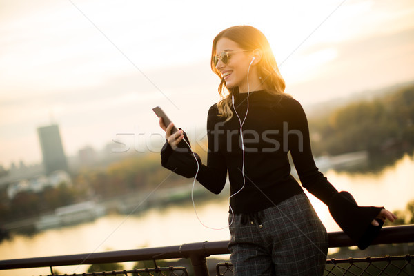 Trendy woman listening music from smartphone outdoor at sunset Stock photo © boggy
