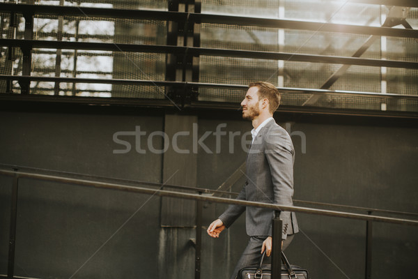 Young handsome man walking by office building Stock photo © boggy