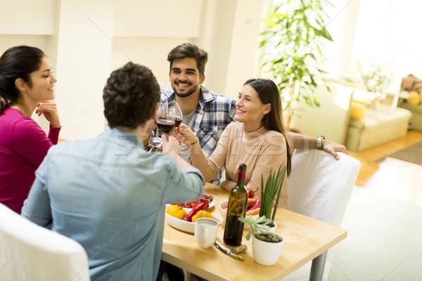 Młodych ludzi posiedzenia tabeli grupy szczęśliwy jedzenie Zdjęcia stock © boggy