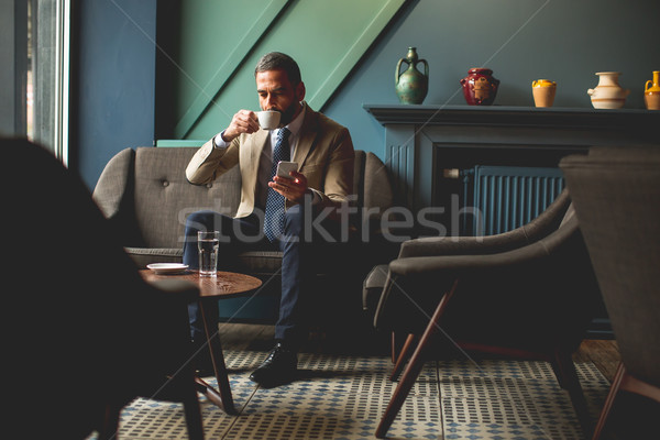 Middle-aged businessman drinking coffee and uses mobile phone in Stock photo © boggy
