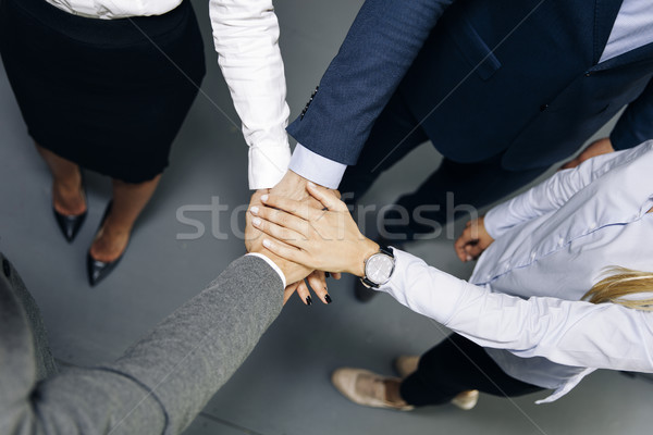 Young coworkers putting hands together as symbol of unity in the Stock photo © boggy