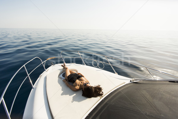 Young attractive woman lies and sunbathing on the bow of a luxur Stock photo © boggy