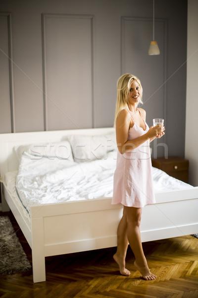 Młoda kobieta szkła wody stwarzające sypialni domu Zdjęcia stock © boggy