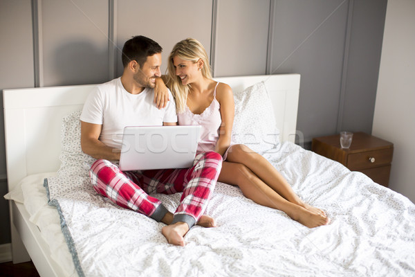 Intimate lovers using laptop sitting on the bed Stock photo © boggy