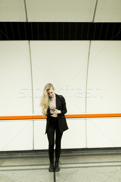 Pretty young woman with mobile phone in a subway Stock photo © boggy