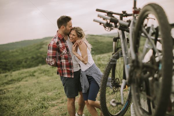 Loving couple stnding next to the car with bicycles Stock photo © boggy