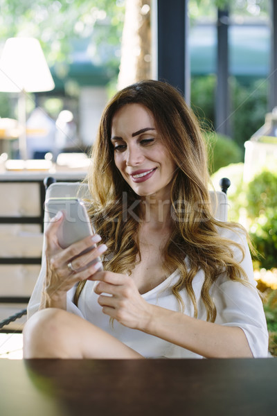 Young woman with smart phone sitting in restaurant Stock photo © boggy