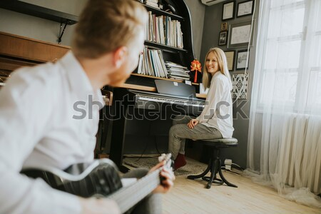 Young piano player accompanied by a male guitarist Stock photo © boggy