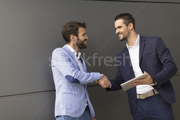 Young businessmen handshaking by the office building Stock photo © boggy