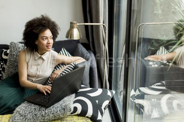 Mulher jovem cabelos cacheados laptop sessão sofá casa Foto stock © boggy