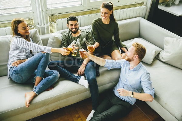 Group of young friends drinking cider and having fun in the room Stock photo © boggy