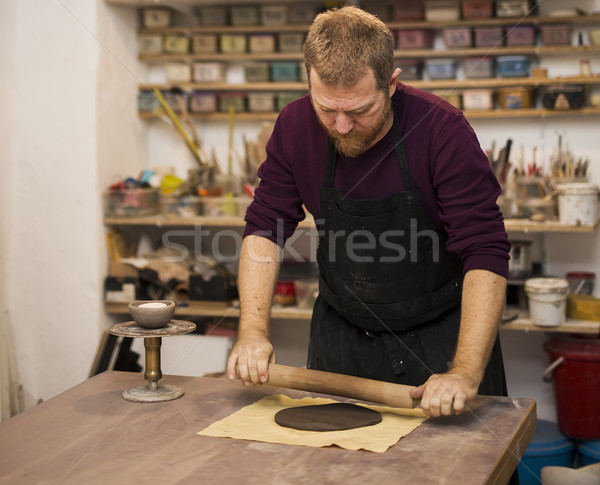 Skilled master preparing clay pieces for his new creations Stock photo © boggy