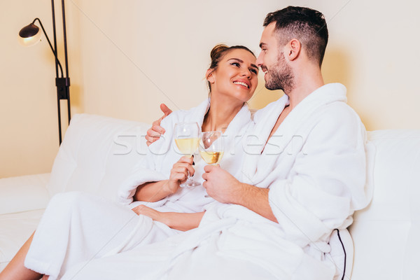 Loving couple drinking white wine in a bathrobe in a spa center Stock photo © boggy