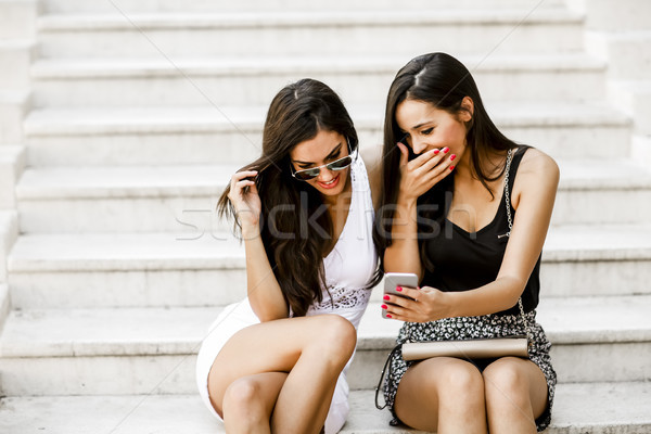 Two young women sitting on the stone steps outside and looking a Stock photo © boggy