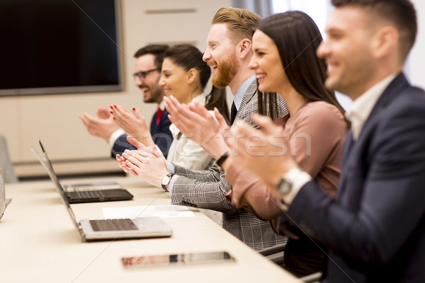 Happy smiling business team clapping hands during a meeting in o Stock photo © boggy