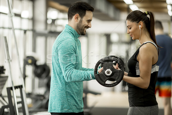 Young woman with personal trainer in gym Stock photo © boggy