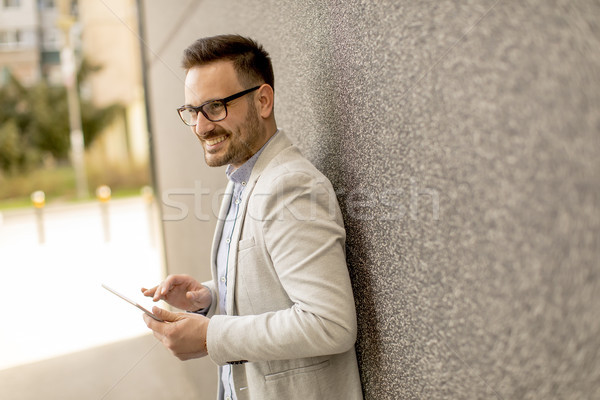 Young businessman with digital tablet by the grey wall Stock photo © boggy