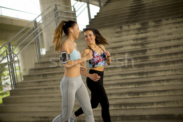 Young women running in urban enviroment Stock photo © boggy