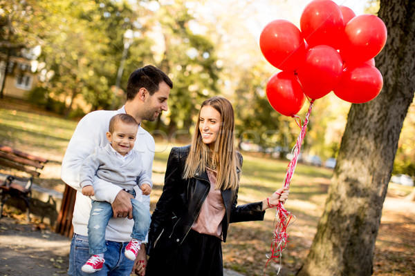 Happy young parents with baby boy in autumn park holding red bal Stock photo © boggy