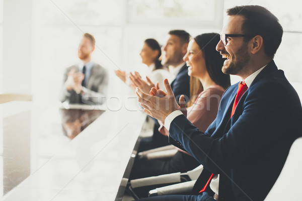 Smiling business group clapping hands at the meeting Stock photo © boggy
