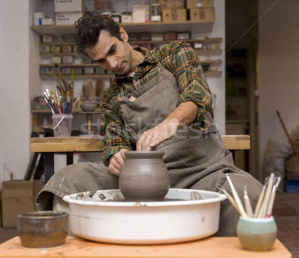 Male artist makes clay pottery on a spin wheel Stock photo © boggy