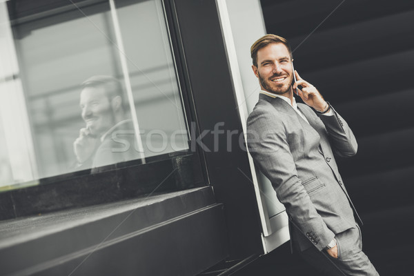 Stock photo: Handsome young man with mobile phone by the office building