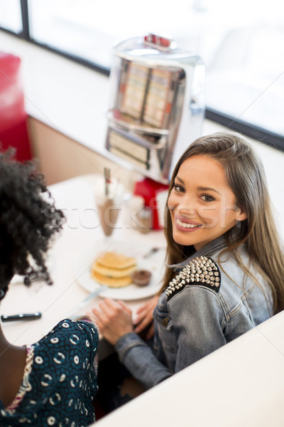 Stock photo: Young woman having lunch in a diner