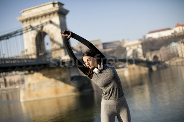 Woman in sportswear stretching on Danube river promenade in Buda Stock photo © boggy