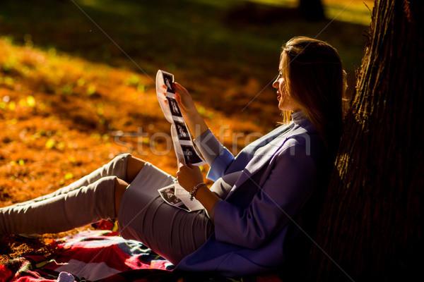 Terhes nő ül ősz park fiatal fa Stock fotó © boggy