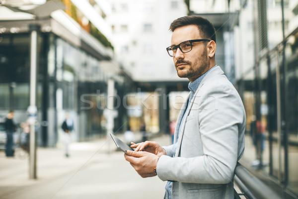 молодые бизнесмен цифровой таблетка офисное здание красивый Сток-фото © boggy