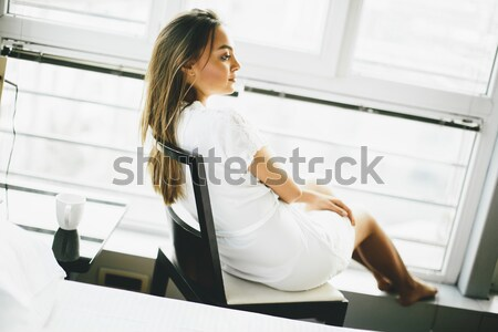 Young woman sitting and daydreaming on a chair by the window Stock photo © boggy