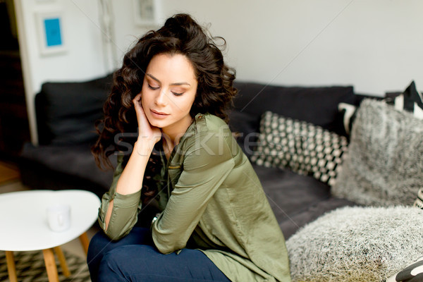 Portrait of a young woman with curly hair relaxes on a sofa in t Stock photo © boggy