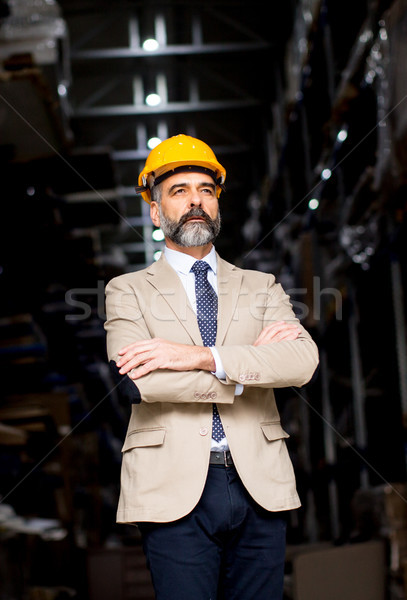 Portrait of handsome businessman withhelmet in a warehouse Stock photo © boggy
