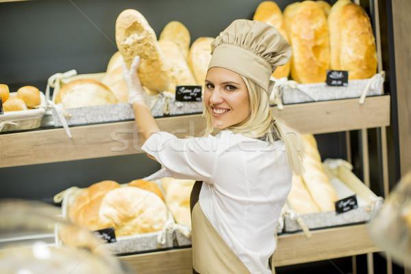 Jeune femme fraîches pain tablettes Baker magasin Photo stock © boggy