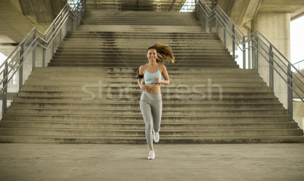 Young woman running in urban enviroment Stock photo © boggy