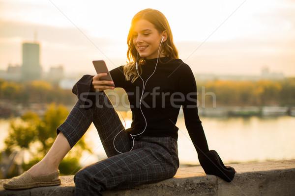 トレンディー 女性 リスニング 音楽 スマートフォン 屋外 ストックフォト © boggy