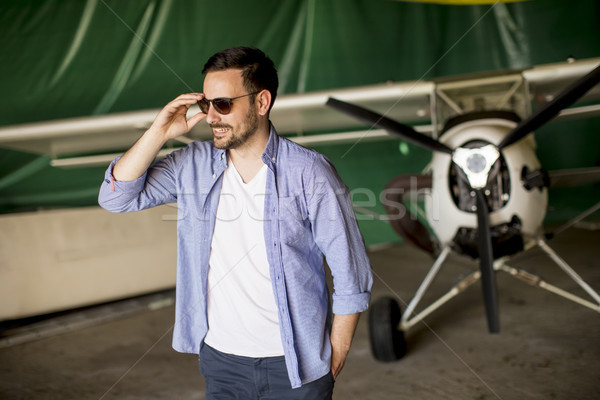 Young man in the airplane hangar Stock photo © boggy