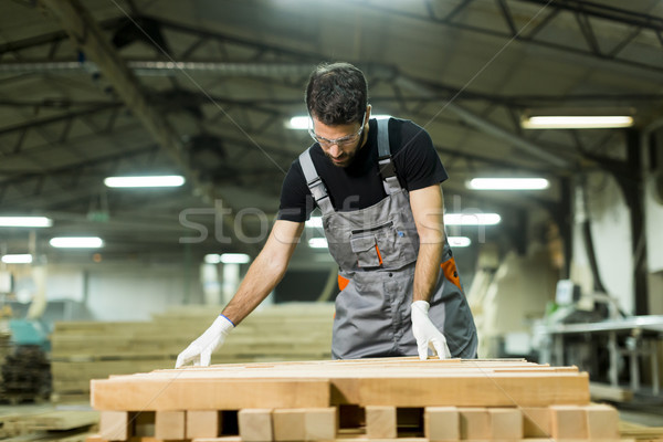 Young worker works in a factory for the production of furniture Stock photo © boggy