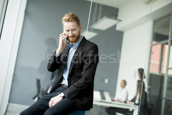 Businessman with ginger hair using mobile phone while other busi Stock photo © boggy