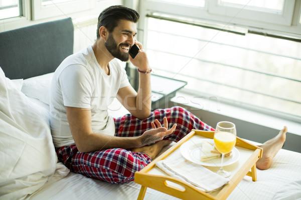 Сток-фото: молодым · человеком · завтрак · кровать · мобильного · телефона · телефон · домой
