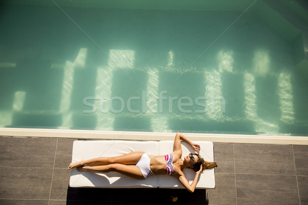 Young woman lying by the pool on sunbed Stock photo © boggy