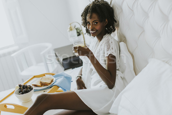 Stock photo: Smiling african american woman having a relaxing breakfast in be