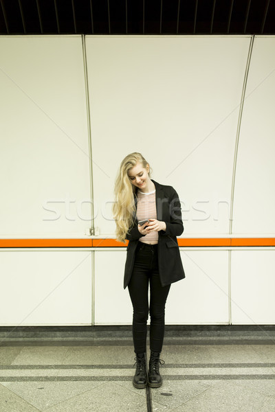 Woman standing on a subway station, waiting for metro and using  Stock photo © boggy