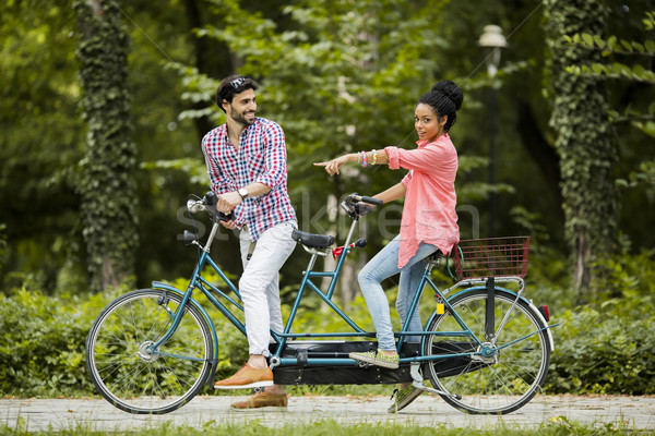 Young couple riding on the tandem bicycle Stock photo © boggy