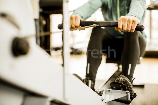 Joven formación gimnasio remo máquina ejercicio Foto stock © boggy